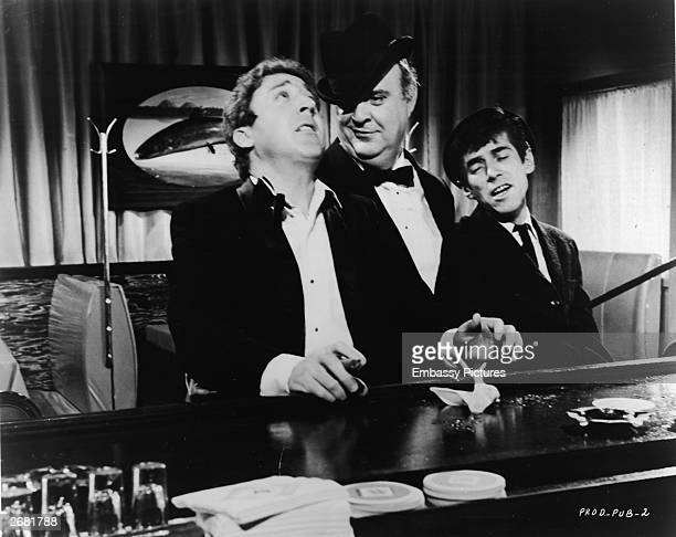 Actors Gene Wilder Zero Mostel and William Hickey sing drunkenly at a bar in a still from the film 'The Producers' directed by Mel Brooks 1968