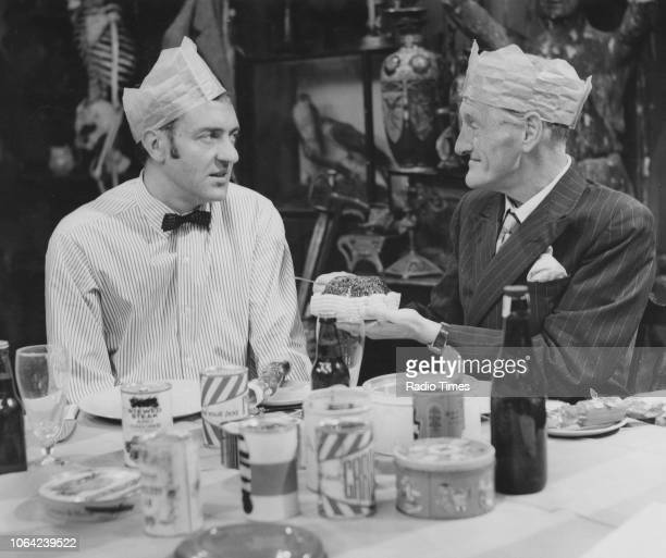 Actors Harry H Corbett and Wilfrid Brambell wearing Christmas hats and eating dinner photographed by Radio Times for the 'Steptoe and Son' Christmas...