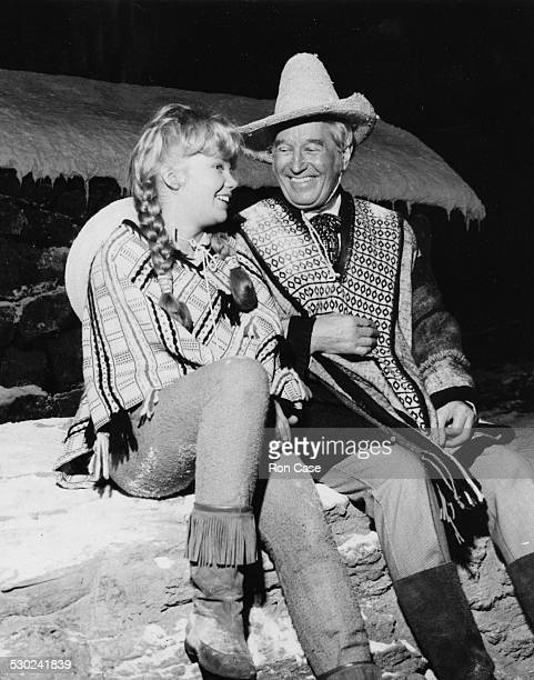 Actors Hayley Mills and Maurice Chevalier laughing during filming on the set of the film 'In Search of the Castaways' at Pinewood Studios' circa 1961