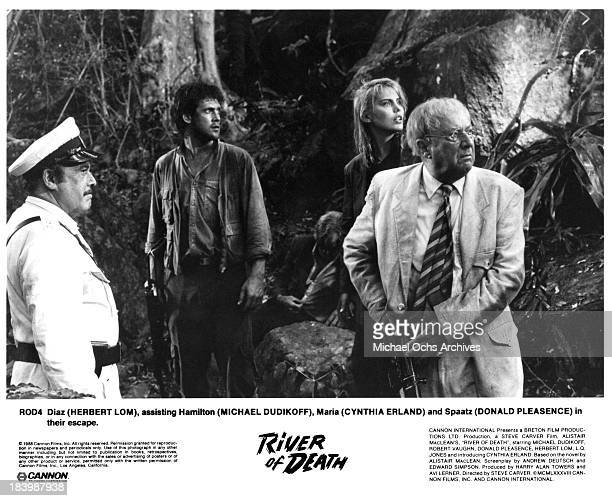 Actors Herbert Lom Michael Dudikoff actress Cynthia Erland actors Donald Pleasence on set of the Cannon Films movie River of Death in 1989