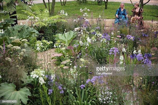 Actors in Shakespearean dress relax in the Lunaria Landscapes garden during the press preview day of the Hampton Court Palace Flower Show on July 4,...