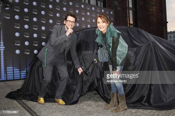 Actors Ingo Naujoks and Anja Kling pose at the covered Volkswagen New Beetle prior to the world premiere of the 21st Century Beetle at ewerk on April...