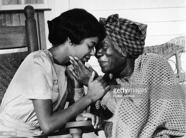 Actors Irene Cara and Beah Richards clasp hands while sitting on a porch in a still from the television miniseries 'Roots' 1977