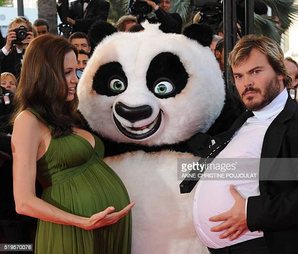 US actors Jack Black and Angelina Jolie pose with a person dressed in a panda costume as they arrive to attend the screening of US directors John...
