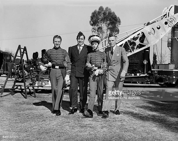 Actors Jackie Cooper Andy Devine Freddie Bartholomew and Henry Hull pose as they walk in the set of Spirit of Culver in Los Angeles California