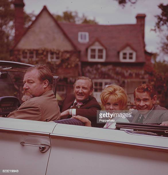 Actors James Robertson Justice Leslie Phillips Sally Smith and Stanley Baxter pictured together in an open top car on the set of the film Father Came...
