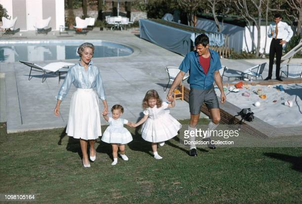 Actors Janet Leigh and Tony Curtis play with their daughters daughters Jamie Lee and Kellyby the pool at home on April 4, 1960 in Los Angeles,...