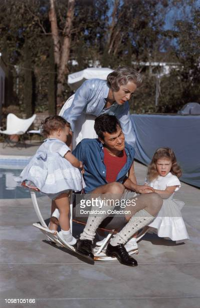 Actors Janet Leigh and Tony Curtis play with their daughters daughters Jamie Lee and Kellyby the pool at home on April 4 1960 in Los Angeles...