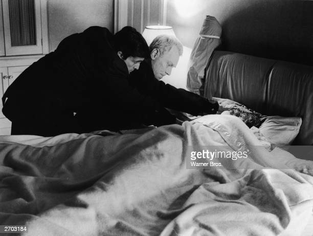 Actors Jason Miller and Max von Sydow place their hands on actress Linda Blair's head while she sleeps in the film 'The Exorcist' directed by William...