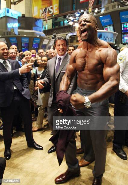 Actors Jason Statham Sylvester Stallone and Terry Crews pose for pictures after ringing the opening bell at the New York Stock Exchange on August 19...