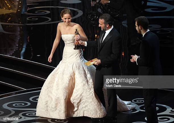 Actors Jennifer Lawrence and Jean Dujardin onstage during the Oscars held at the Dolby Theatre on February 24, 2013 in Hollywood, California.