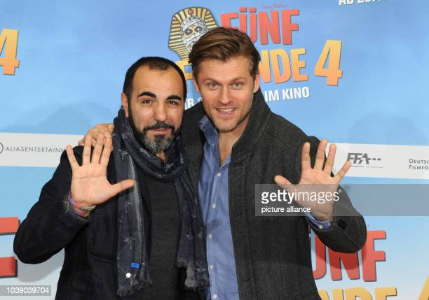 Actors Jens Atzhorn  and Adnan Maral pose in front of the movie poster at the premiere of 'Fuenf Frende 4' at the Cinemaxx in Munich Germany 25...