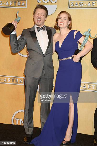 Actors Jeremy Renner and Amy Adams pose in the press room during the 20th Annual Screen Actors Guild Awards at The Shrine Auditorium on January 18...