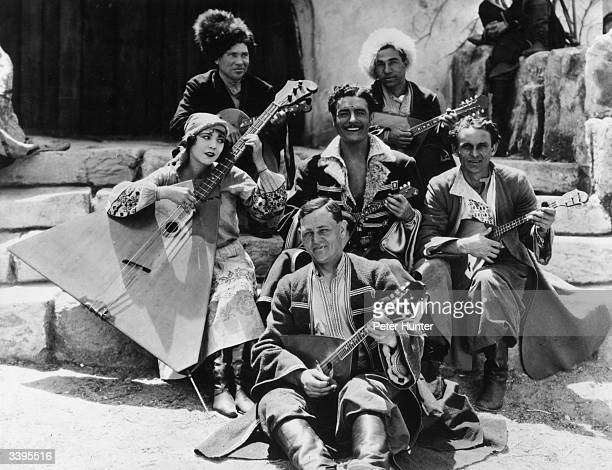 Actors John Gilbert and Renee Adoree pose with a troupe of Russian musicians during the filming of the MGM production 'The Cossacks' Renee is playing...