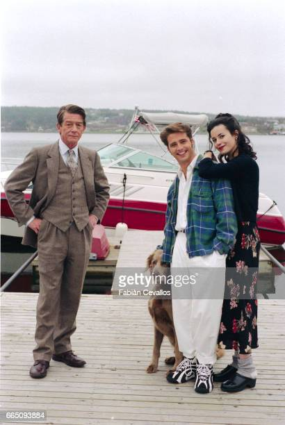 Actors John Hurt in a suit and tie Jason Priestley wearing sneakers and comfortable clothes with a dog next to him and Fiona Loewi wearing clogs and...