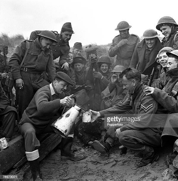 Actors John Mills receives a drink from Richard Attenborough during the making of a film about the Dunkirk evacuation 1957