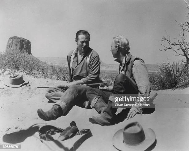 Actors John Wayne as Ethan Edwards and Harry Carey Jr as Brad Jorgensen in The Searchers