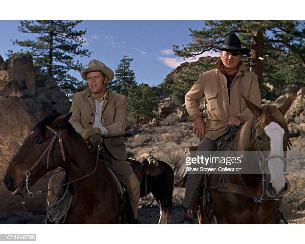Actors John Wayne as Rooster Cogburn and Glen Campbell as La Boeuf in a scene from the western 'True Grit' 1969