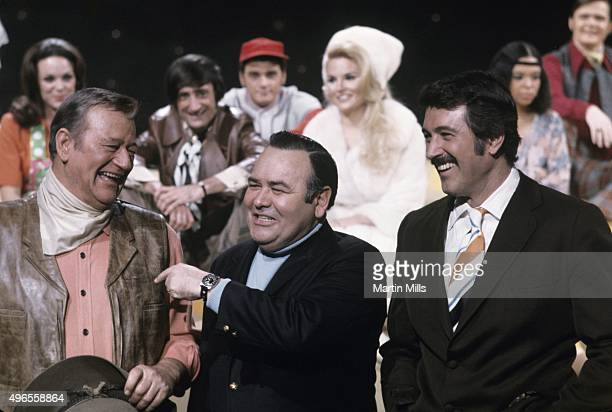 Actors John Wayne Jonathan Winters and Rock Hudson on the set of an unaired NBC TV special 'Wrap Up' in 1969 in Los Angeles California