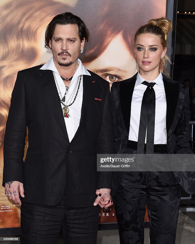 Actors Johnny Depp and Amber Heard arrive at the premiere of Focus Features' 'The Danish Girl' at Westwood Village Theatre on November 21, 2015 in Westwood, California.