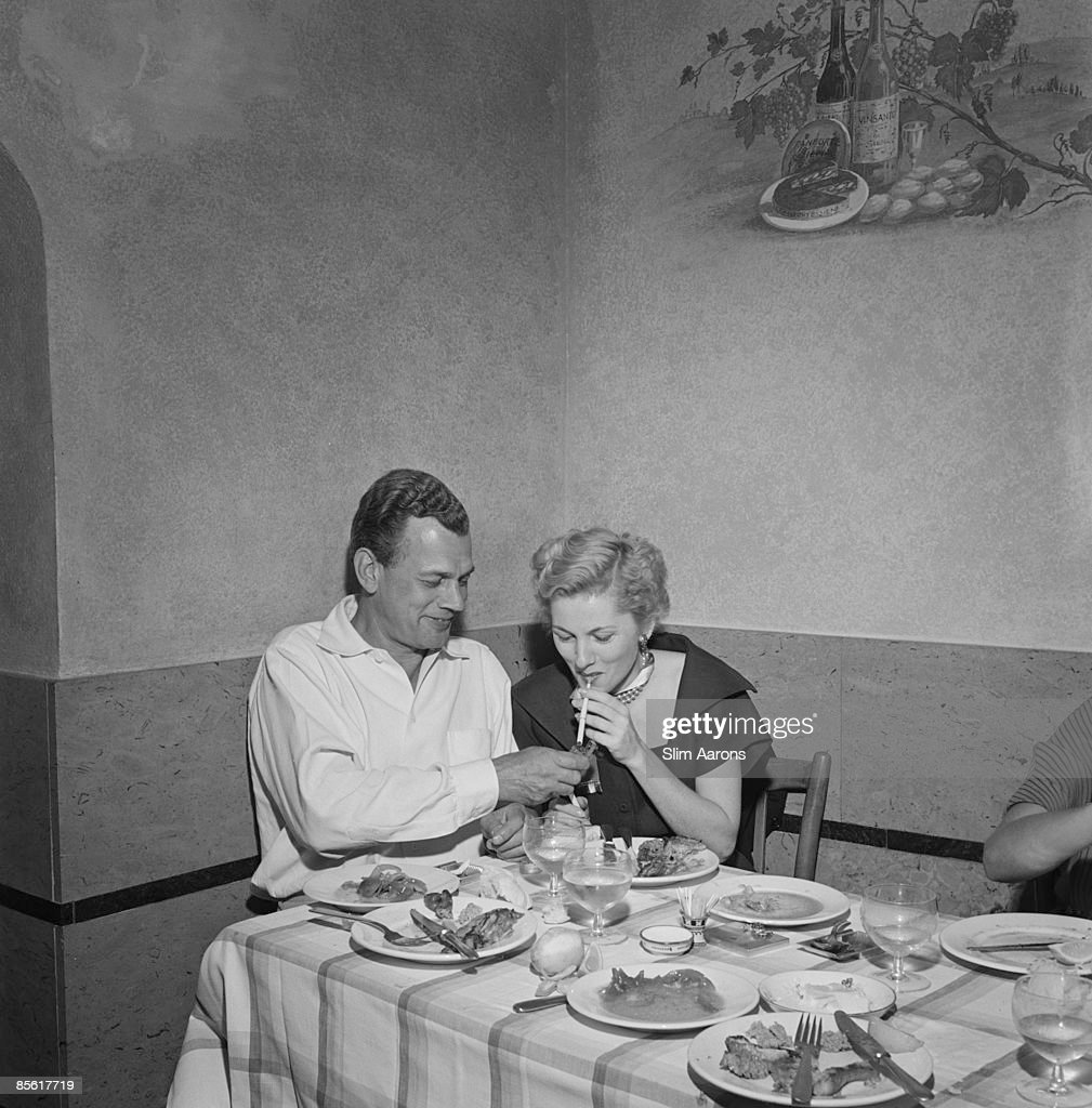 Actors Joseph Cotten (1905 - 1994) and Joan Fontaine eat out at a restaurant in Italy, during the location filming of 'September Affair', August 1949.