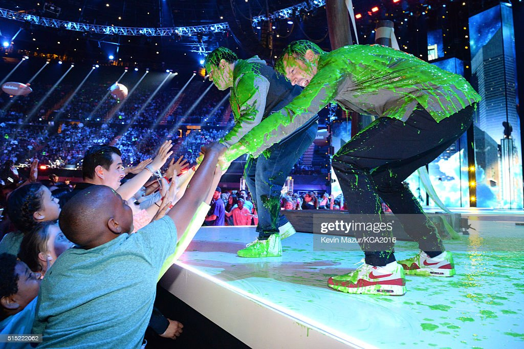 Actors Josh Gad (onstage L) and Jason Sudeikis (onstage R) greet fans after getting slimed during Nickelodeon's 2016 Kids' Choice Awards at The Forum on March 12, 2016 in Inglewood, California.