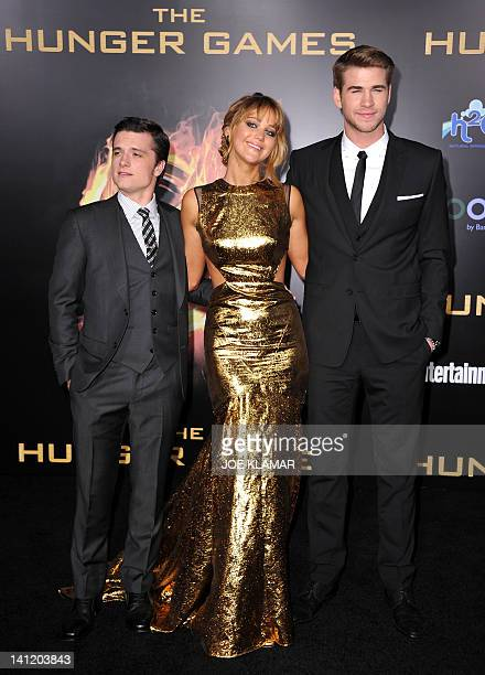 Actors Josh Hutcherson Jennifer Lawrence and Liam Hemsworth pose for a picture as they arrive at the premiere of Lionsgate's 'The Hunger Games' at...