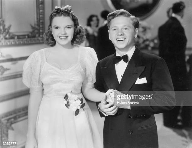 Actors Judy Garland and Mickey Rooney hold hands in a still from the film 'Andy Hardy Meets a Debutante' directed by George B Seitz