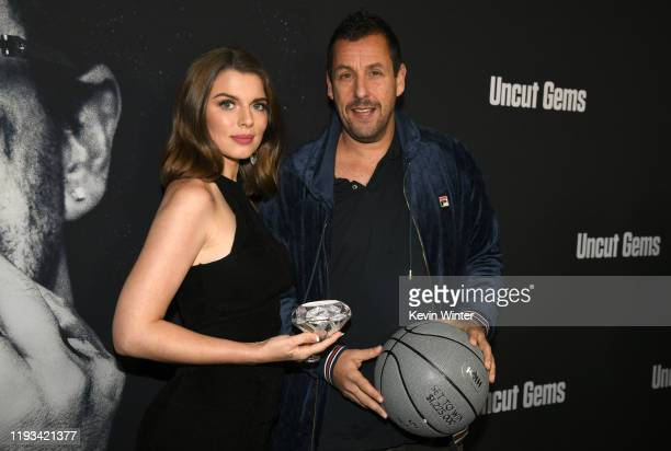 Actors Julia Fox and Adam Sandler at the premiere of A24's Uncut Gems at The Dome at Arclight Hollywood on December 11 2019 in Hollywood California