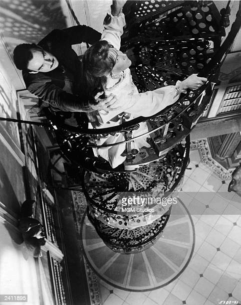 Actors Julie Harris and Richard Johnson ascend a spiral wrought iron staircase in a still from the film 'The Haunting' directed by Robert Wise 1963