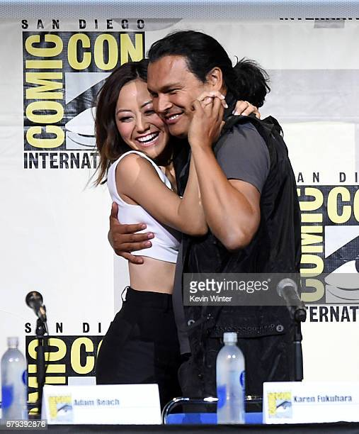 Actors Karen Fukuhara and Adam Beach attend the Warner Bros Presentation during ComicCon International 2016 at San Diego Convention Center on July 23...