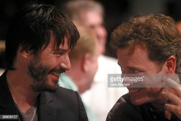 Actors Keanu Reeves and Greg Kinnear talk to each other during the 'Lights Camera Fashion 2' show on June 4 2004 in Austin Texas