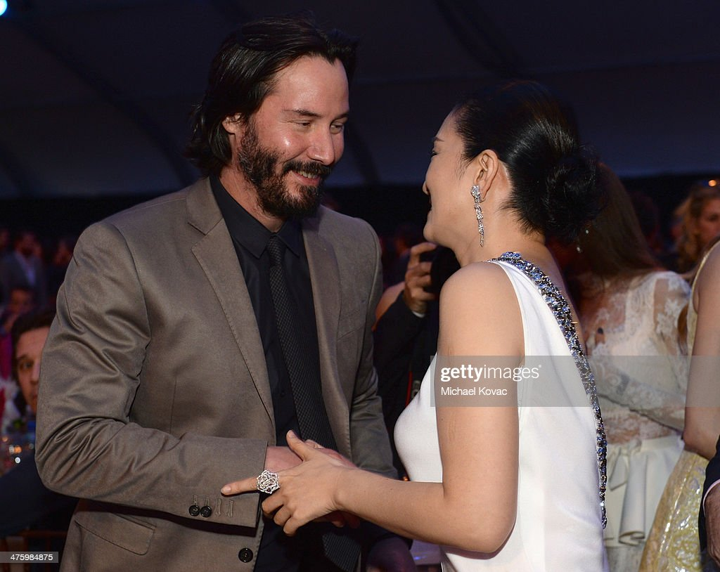 Actors Keanu Reeves (L) and Li Gong, wearing Piaget, attend the 2014 Film Independent Spirit Awards at Santa Monica Beach on March 1, 2014 in Santa Monica, California.
