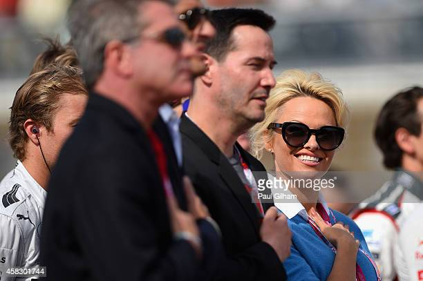 Actors Keanu Reeves and Pamela Anderson stand for the national anthem before the United States Formula One Grand Prix at Circuit of The Americas on...