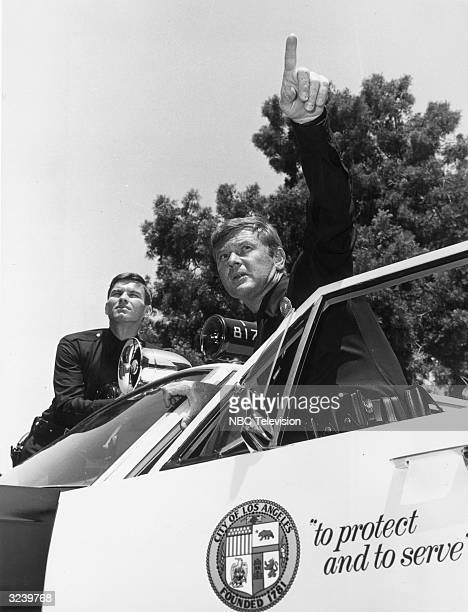 Actors Kent McCord and Martin Milner emerge from a City of Los Angeles police car in a still from the TV series 'Adam 12' The car bears the LAPD...