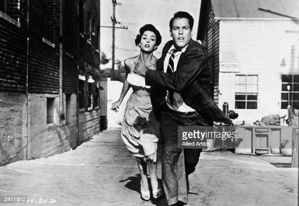 Actors Kevin McCarthy and Dana Wynter run for their lives in a still from the film 'Invasion of The Bodysnatchers' directed by Don Siegel 1956