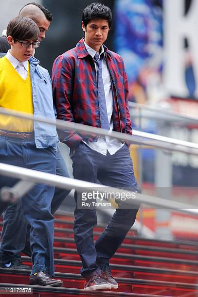 """Actors Kevin McHale and Harry Shum Jr. Film on the set of """"Glee"""" in Times Square on April 25, 2011 in New York City."""