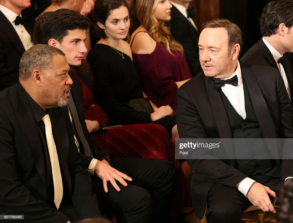 Actors Kevin Spacey (R) and Laurence Fishburne attend a ceremony for the 2016 Kennedy Center honorees December 4, 2016 in the East Room of the White House in Washington, DC. The honorees include Eagles band members, actor Al Pacino, singer James Taylor, pianist Martha Argerich and singer Mavis Staples.
