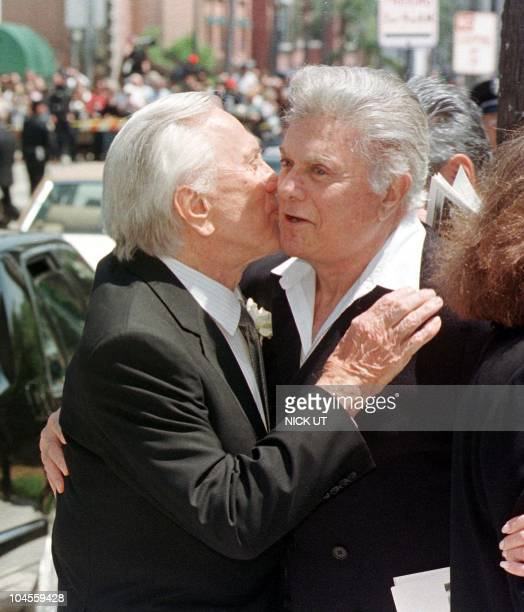 Actors Kirk Douglas and Tony Curtis hug following the funeral of entertainer Frank Sinatra at the Good Sheperd Catholic Church in Beverly Hills 20...