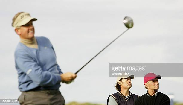 Actors Kyle MacLachlan and Michael Douglas watch as Colin Montgomerie of Scotland tees off on the 17th hole during the second round of the Dunhill...