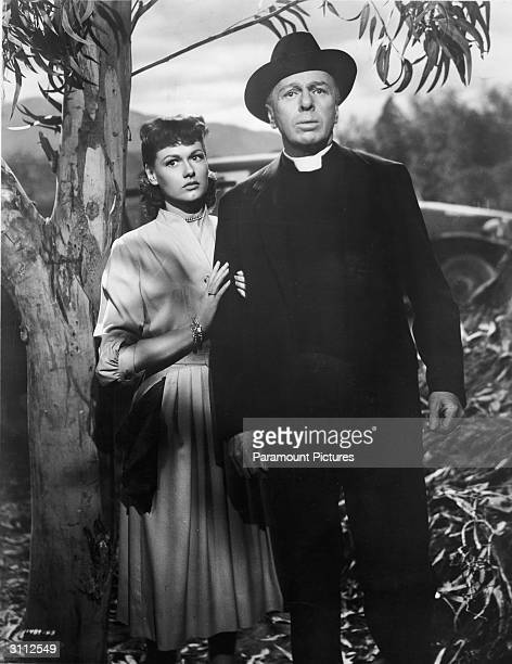 Actors Lewis Martin and Ann Robinson stand by a tree looking with fear in a still from the film 'The War Of The Worlds' directed by Byron Haskin 1953