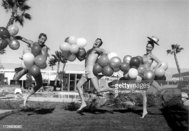 Actors Lloyd Bridges, Hugh O'Brian and Carolyn Jones pose for a portrait wearing balloons at the pool of the co-owned hotel called Whispering Waters...