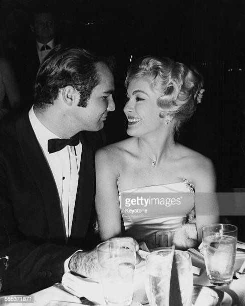 Actors Lori Nelson and Burt Reynolds pictured looking in to each others eyes at a party in Hollywood CA circa 1960