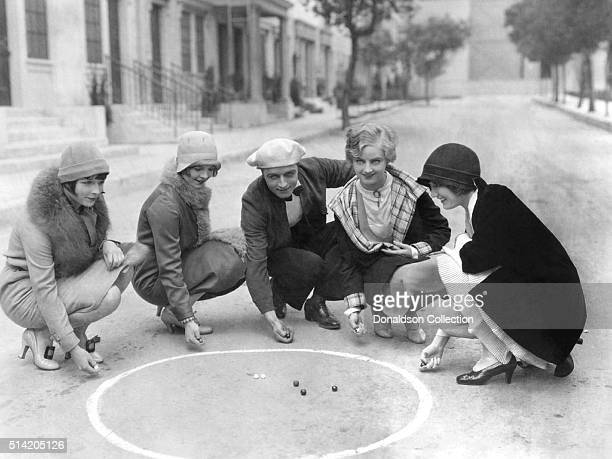 Actors Louise Brooks Nancy Phillips James Hall Doris Hill and Josephone Dunn play marbles at the movie studio in 1927