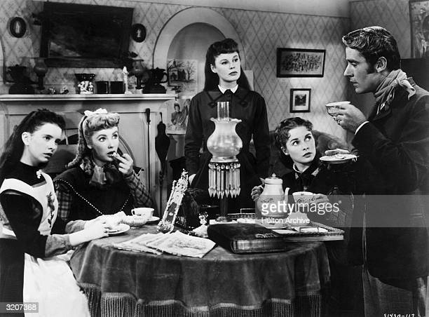 actors Margaret O'Brien Elizabeth Taylor June Allyson Janet Leigh and Peter Lawford sit around a table having tea in a still from director Mervyn...