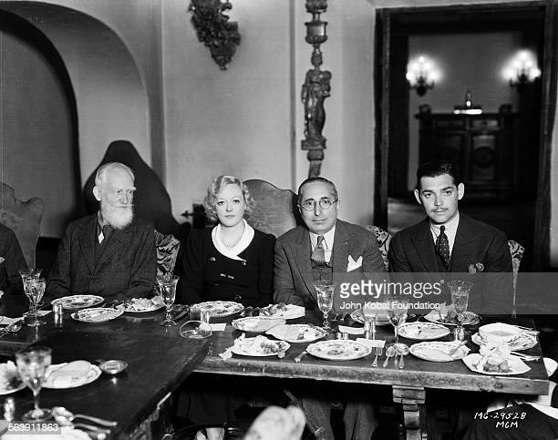 Actors Marion Davies and Clark Gable flanking producer Louis B Meyer with writer George Bernard Shaw on the left all attending a dinner party for MGM...