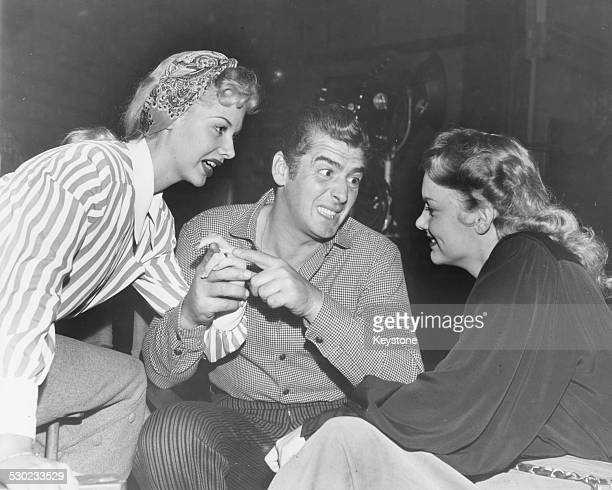 Actors Marion Marshall Vic Mature and Barbara Lawrence chatting on the set of the film 'Ballad of Furnace Creek' circa 1950