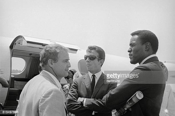Actors Marlon Brando Anthony Franciosa Negro athleteactor Rafer Johnson chat beside a chartered jet plane as they await the arrival of entertainer...