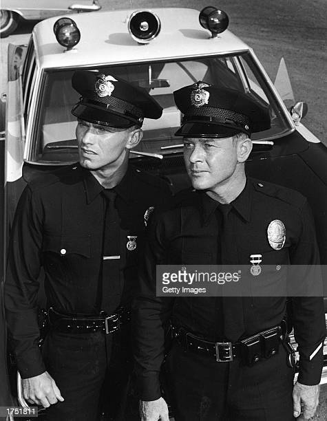 Actors Martin Milner and Kent McCord stand in uniform by their patrol car in a promotional still for the television series 'Adam 12' c 1969
