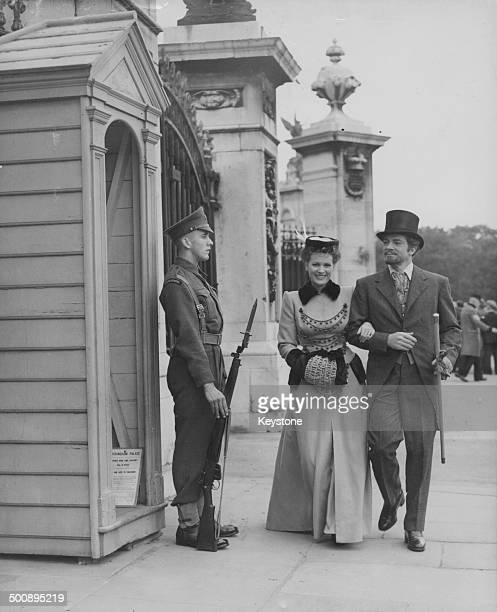 Actors Maureen O'Hara and Dana Andrews in costume during the filming of the movie 'Brittania Mews' walking past the guards at Buckingham Palace...